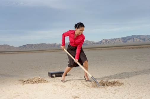 Businesswoman digging hole in dry lake bed