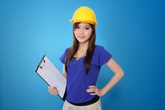 young-asian-architect-woman-yellow-hard-hat-vibrant-blue-background-safety-helmet-holding-work-plan-sheet-53584024