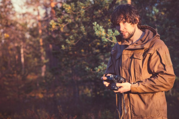 Young Man with retro photo camera outdoor Travel Lifestyle forest nature on background